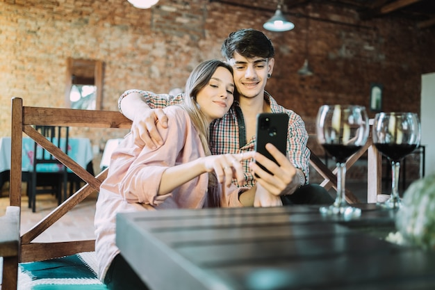 Young couple takes a selfie - young smiling couple hug and enjoy their date on valentine's day.