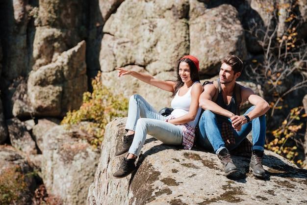 上り坂をハイキングし、人差し指を向けた後、休憩を取っている若いカップル