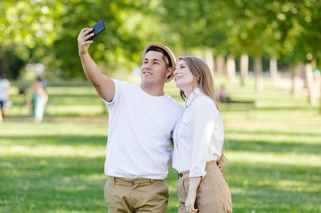 Молодая пара, делающая селфи на свой мобильный телефон в парке. латинский мужчина и кавказская женщина