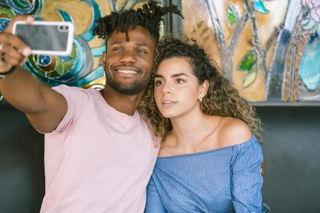 Молодая пара, делающая селфи с мобильным телефоном, сидя в ресторане.