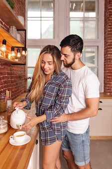 Young couple taking breakfast at the kitchen