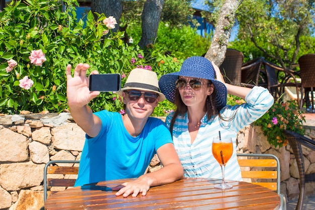 Young couple taking photo with smartphone in outdoor cafe