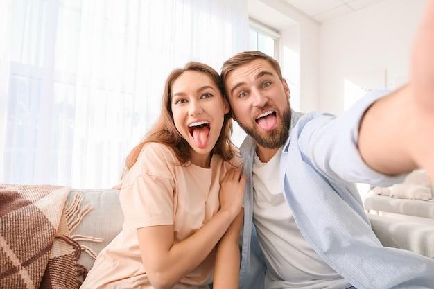 家で自分撮りをしている若いカップル