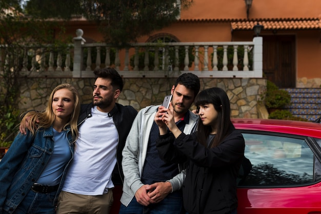 Young couple taking selfie in front of car