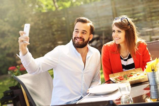 레스토랑에서 selfie를 복용하는 젊은 부부