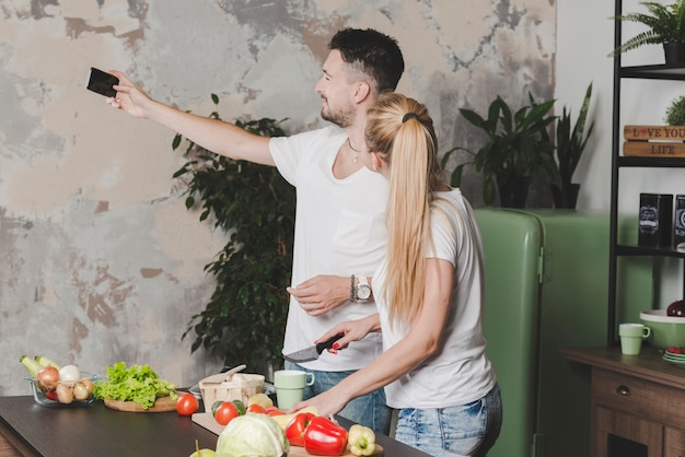 Young couple taking selfie on mobile phone while cutting vegetables