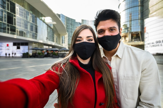 Young couple taking a selfie portrait together outdoor and wearing masks to prevent coronavirus covid 19 pandemic