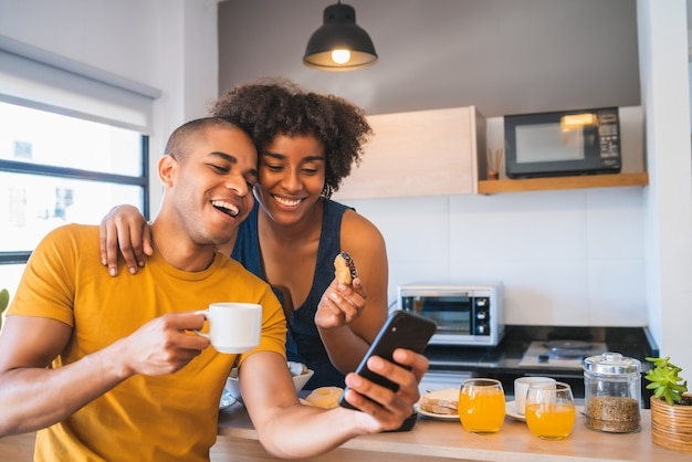 自宅で朝食をとりながらselfieを取る若いカップル。