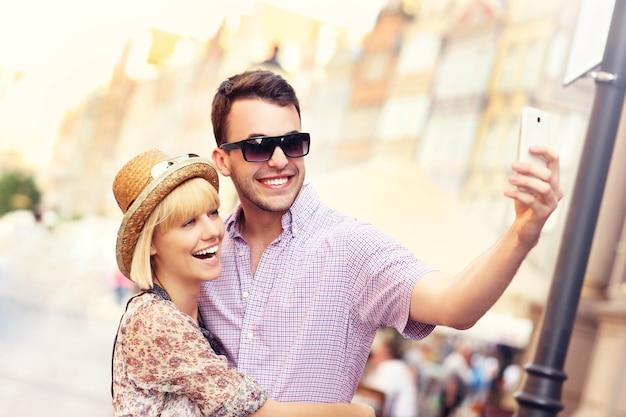 ポーランドのグダニスクを観光しながら自分撮りをしている若いカップル