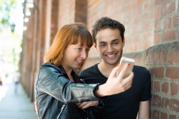 Young couple taking selfie with mobile phone outdoors.