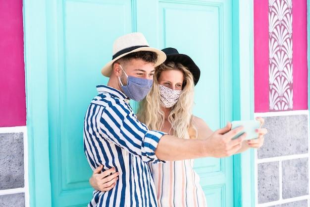 Молодая пара делает селфи в защитных масках на открытом воздухе во время вспышки коронавируса