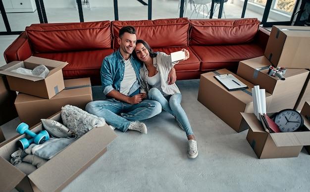 새 집에서 스마트폰으로 셀카를 찍는 젊은 부부. 이사, 집 구입, 아파트 개념.