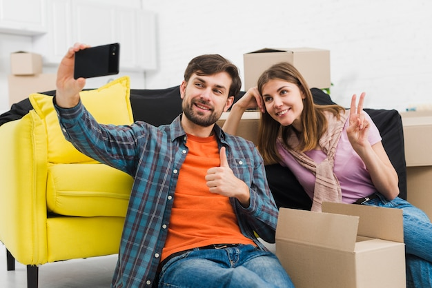 Young couple taking sulfide on mobile phone sitting with cardboard boxes in their new house