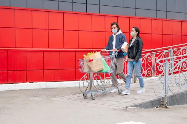Молодая пара разговаривает после посещения супермаркета, идя к своей машине
