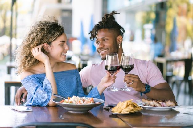 レストランで一緒にランチデートをしながら話したり楽しんだりする若いカップル。