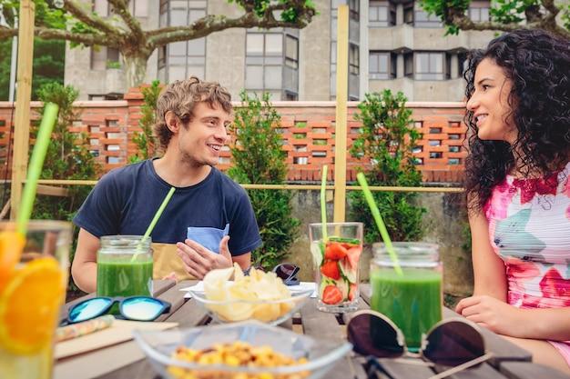 余暇の夏の日の屋外で健康的な飲み物を飲みながらテーブルの周りで話したり笑ったりする若いカップル