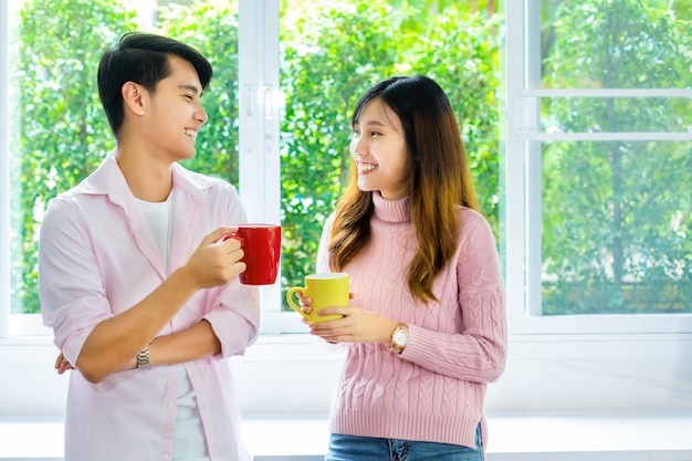 Young couple talking and drink beverage at home