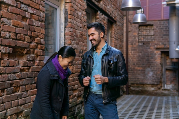 Young couple talking and laughing in the old bystreet