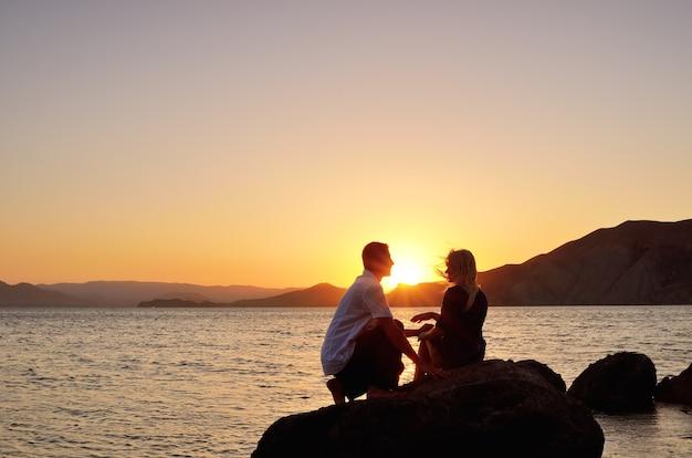 夕日の海のそばの岩の上で話している若いカップル