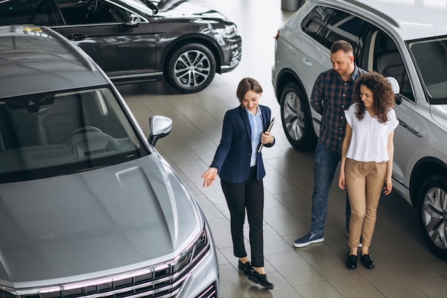 Young couple talking to a sales person in a car showroom