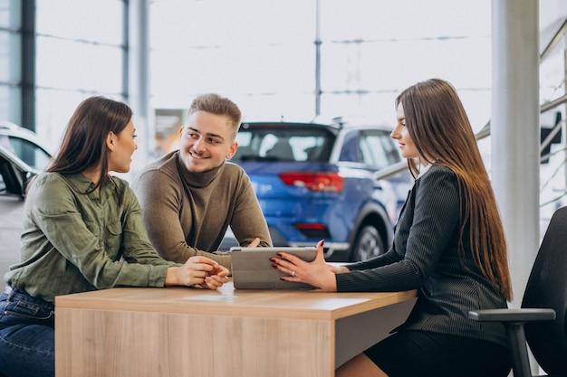 Giovani coppie che parlano con un addetto alle vendite in una sala d'esposizione dell'automobile