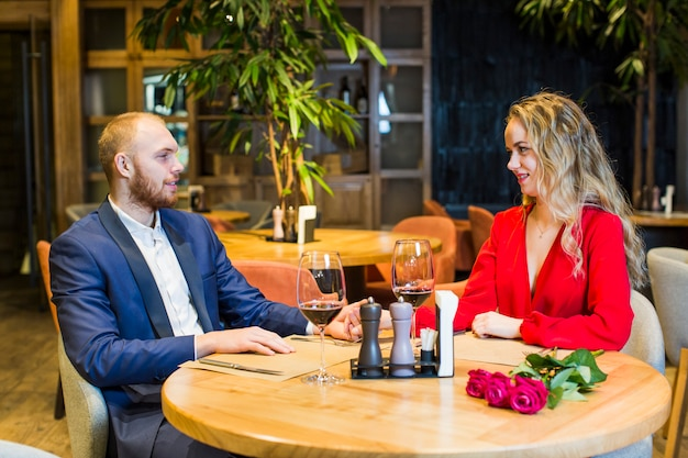 Young couple talking at table in restaurant