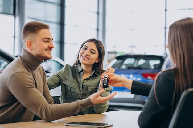 車のショールームで営業担当者に話している若いカップル
