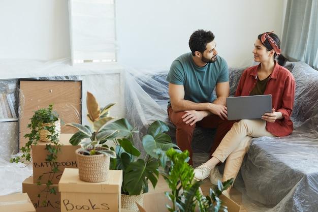 젊은 부부는 서로 이야기하고 새 아파트에서 소파에 앉아있는 동안 노트북을 사용합니다.