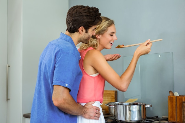 Young couple tasting meal in kitchen at home