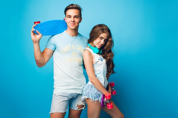 Young couple of teenagers posing on blue background in studio. they wear t-shirts, jeans shorts, hold skateboards and look to camera.