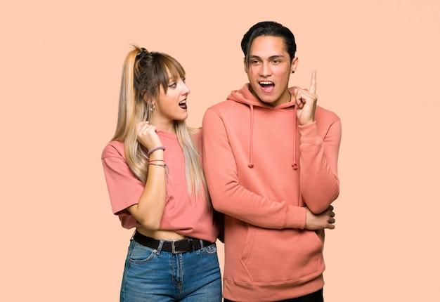 Молодая пара, думая, идея, указывая пальцем на розовом фоне