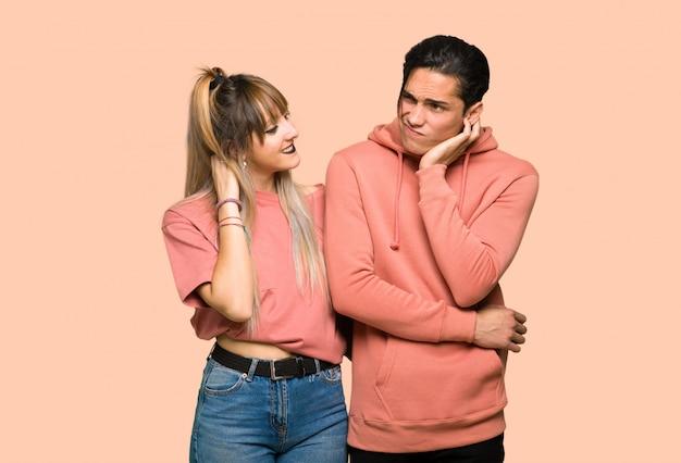 Молодая пара думает идея, почесывая голову на розовом фоне