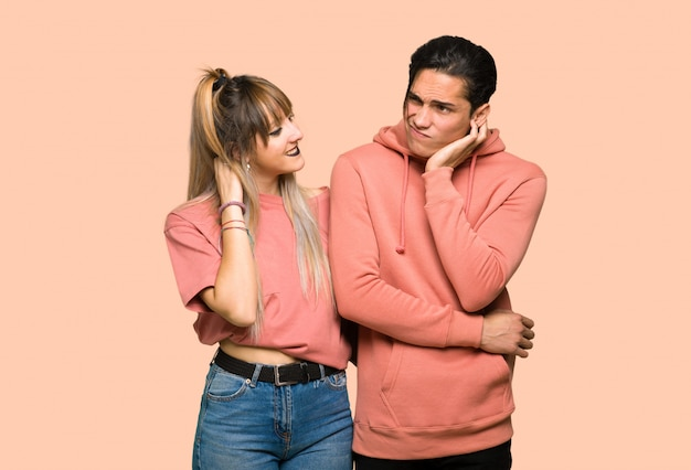 Young couple thinking an idea while scratching head over pink background
