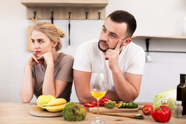 Young couple thinking at the kitchen