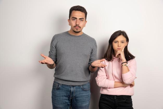 Giovani coppie che pensano su bianco.