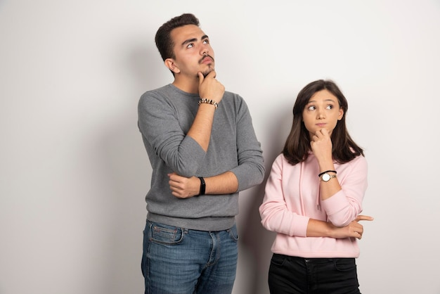 Young couple thinking on white.