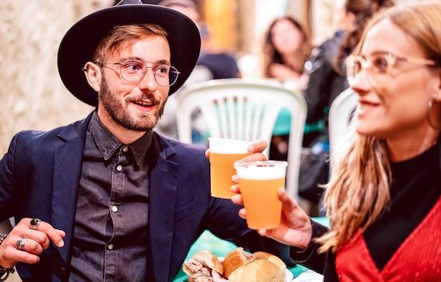 거리 음식 축제에서 맥주 잔을 토스트하는 젊은 부부-친구가 맥주 술집에서 행복한 시간에 함께 재미와 음료 라이프 스타일 개념