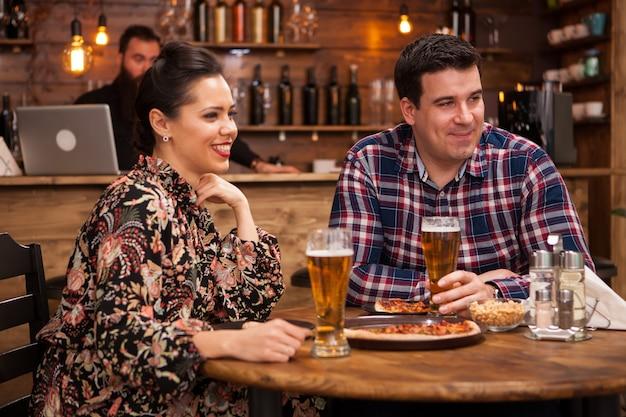 一緒に素晴らしい時間を過ごしている若いカップル。美味しいピザ。