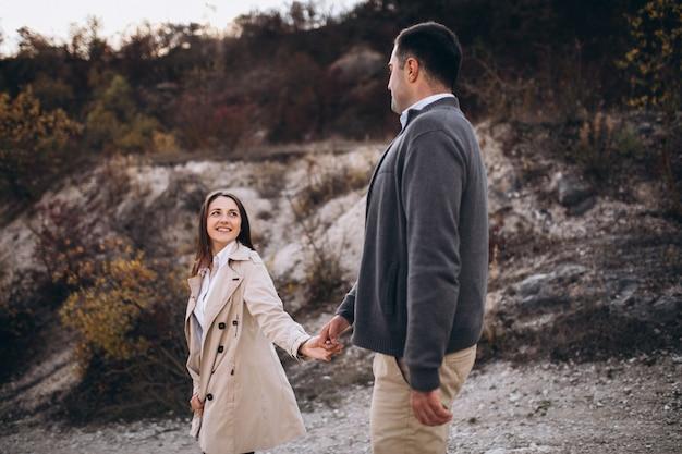 秋の自然の中で一緒に若いカップル