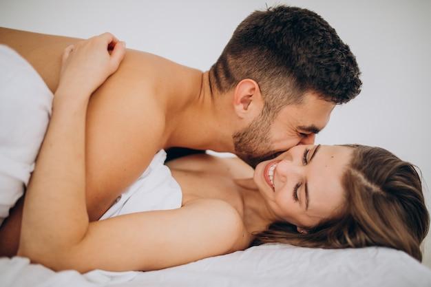 Молодая пара вместе лежа в постели