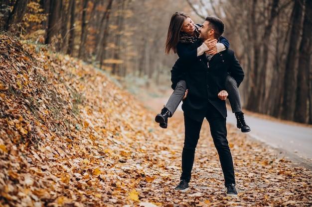 Giovani coppie che camminano insieme in un parco in autunno