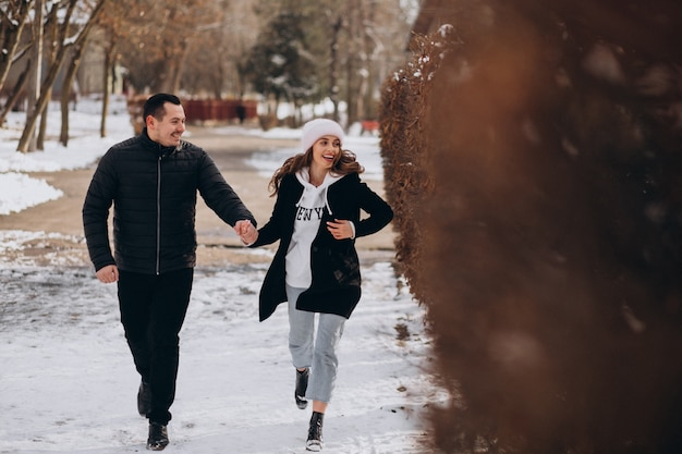 Young couple together in a winter park on valentines day
