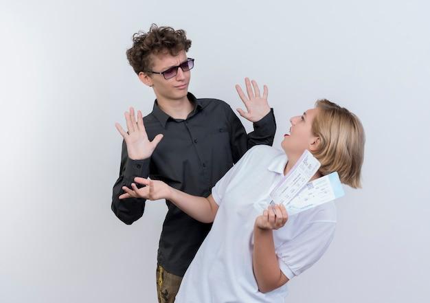 Giovane coppia di turisti uomo confuso e scontento guardando la sua ragazza con i biglietti aerei nelle mani in piedi sopra il muro bianco