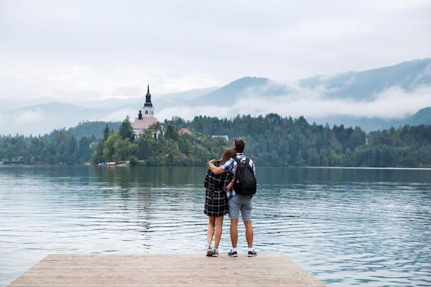 Young couple of tourists in love on the lake bled slovenia autumn time in europe