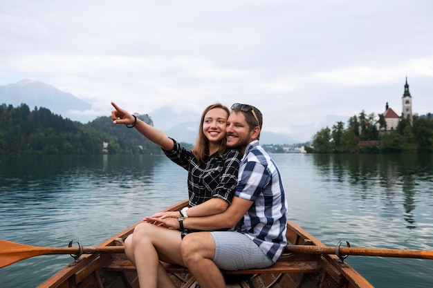 Young couple of tourists in love on traditional wooden boat on the lake bled slovenia