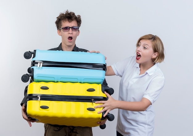 Young couple of tourists man holding heavy suitcases being surprised while his girlfriend trying to help over white