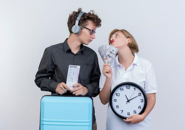 Giovane coppia di turisti uomo con le cuffie che tengono la valigia e biglietti aerei in piedi accanto alla sua ragazza con contanti e orologio da parete guardando a vicenda con espressione triste sopra il muro bianco