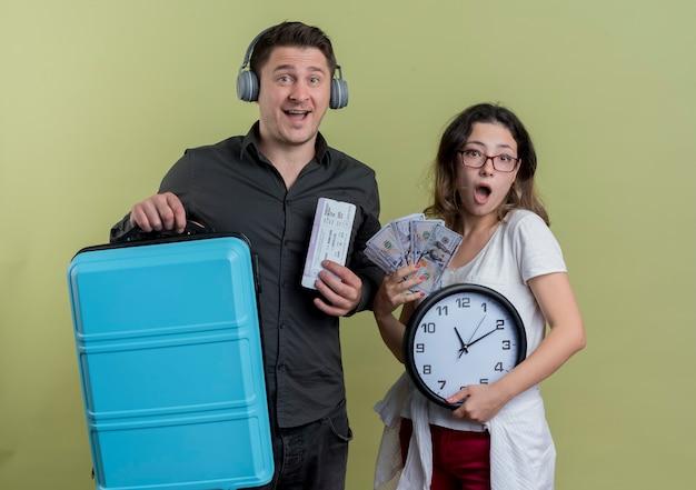 Giovane coppia di turisti uomo con le cuffie che tengono la valigia e biglietti aerei in piedi accanto alla sua ragazza con denaro contante e orologio da parete sorpreso sulla parete chiara