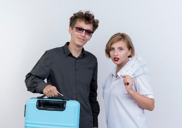 Giovane coppia di turisti uomo e donna che tiene la valigia e biglietti aerei con facce serie in piedi sopra il muro bianco