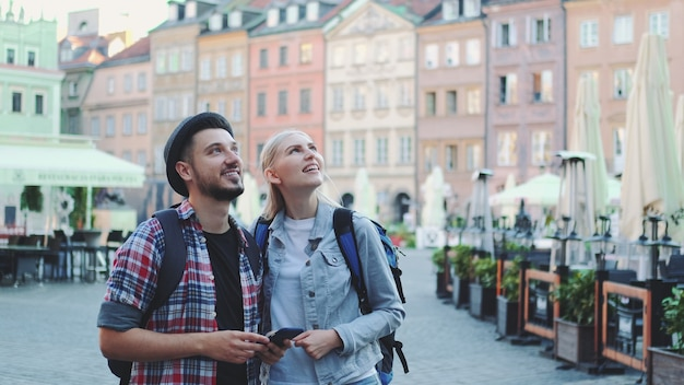Young couple of tourists using smartphone and admiring beautiful surroundings